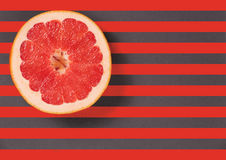 Red juicy grapefruit on a striped background top view Royalty Free Stock Photography