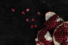 Red juicy pomegranate on dark marble background. Healthy, antioxidant, fresh, gourmet, delicious, organic fruit. Ingredient for grenadine. Close-up and copy Royalty Free Stock Photos