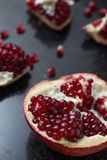 Red juicy pomegranate on dark marble background. Healthy, antioxidant, fresh, gourmet, delicious, organic fruit. Ingredient for grenadine. Close-up and copy Stock Images