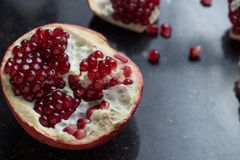 Red juicy pomegranate on dark marble background. Healthy, antioxidant, fresh, gourmet, delicious, organic fruit. Ingredient for grenadine. Close-up and copy Stock Photos
