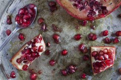 Red and juicy pomegranate and grains Stock Image