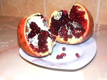 Red juicy pomegranate on a plate royalty free stock image