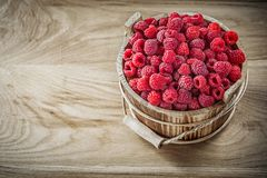 Red juicy raspberries in bucket on wooden board.  Stock Photo