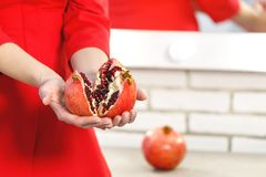 Red juicy ripe pomegranate in female hands. royalty free stock image