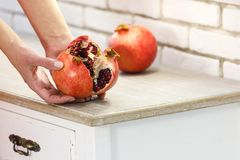 Red juicy ripe pomegranate in female hands. Fault. royalty free stock photography