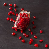 Red juicy ripe pomegranate grains on dark wooden background. Royalty Free Stock Images