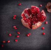 Red juicy ripe pomegranate grains on dark wooden background. Stock Photos