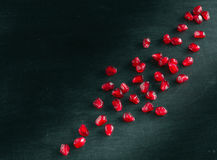 Red juicy ripe pomegranate grains on dark wooden background. Stock Images