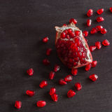 Red juicy ripe pomegranate grains on dark wooden background. Stock Image