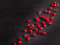 Red juicy ripe pomegranate grains on dark wooden background. Royalty Free Stock Photos