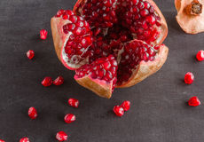 Red juicy ripe pomegranate grains on dark wooden background. Stock Photography