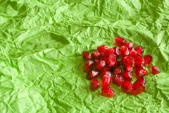Red juicy ripe pomegranate grains on green paper background. Stock Images