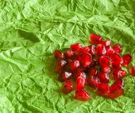 Red juicy ripe pomegranate grains on green paper background. Royalty Free Stock Photos