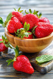 Red juicy strawberries in a wooden bowl closeup. Royalty Free Stock Photography