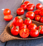 Red juicy tomatoes cherry in brown wooden plate Royalty Free Stock Photo