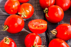Red juicy tomatoes cherry on dark wooden board Stock Photography