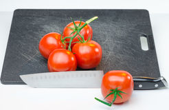 Red juicy tomatoes on Cutting Board Stock Image