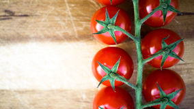Red juicy tomatoes on a cutting board. Red juicy tomatoes on a wooden cutting board Royalty Free Stock Image