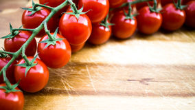 Red juicy tomatoes on a cutting board. Red juicy tomatoes on a wooden cutting board Royalty Free Stock Photography