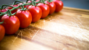 Red juicy tomatoes on a cutting board. Red juicy tomatoes on a wooden cutting board Royalty Free Stock Images
