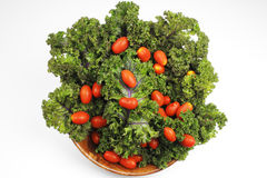 Red Kale, Cherry Tomatoes. Small red cherry tomatoes on top of red kale in a wood bowl on white background Stock Images