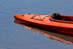 Red Kayak. The bow of a red kayak in a blue lake stock photo