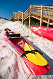Red Kayak. In the sands on a beach besides a wooden staircase Royalty Free Stock Photo