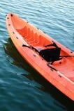 Red kayak on dark river water.  Royalty Free Stock Photo