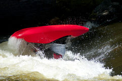 A red kayak flips as a paddler does his stunts. Royalty Free Stock Photos