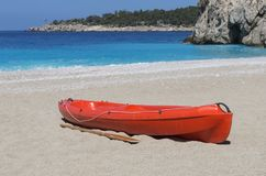 Red kayak with a paddle close-up on an empty sandy beach. Against a turquoise sea and the rocky shore stock photo
