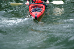 Red kayak  in rough water, front view, leisure and water sports Stock Photography