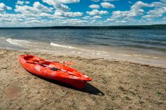 Red kayak stands on a sandy shore by the lake stock photography