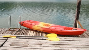 Red kayak on wood floor. And lake stock images