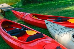 Boats at the dock, red kayaks on the shore. Red kayaks on the shore, boats at the dock Stock Photos