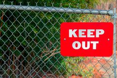 A Red Keep Out Sign on a Fance. Here is a red keep out sign hanging on a fence royalty free stock photography