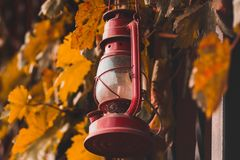 Red kerosene lamp on the fence with leaves. Background old lantern antique object ancient wooden equipment fuel metal vintage outdoor handle rustic wall oil stock photography