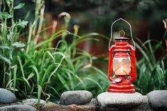 Red kerosene lamp isolated on garden background Royalty Free Stock Photos