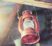 Red kerosene lantern hanging on for so long. Stock Photo