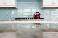 Red Kettle glass backsplash subway tile kitchen. Red kettle kitchen glass subway tile backsplash granite countertop stock images