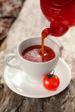 Red kettle is pouring tomato juice in a white Cup Royalty Free Stock Photo