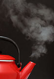 Red kettle steaming hot. On black background Royalty Free Stock Image