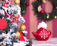 Red kettle with tea at Christmas tree Royalty Free Stock Photo