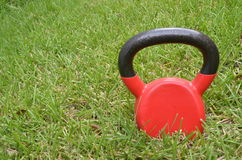 Red kettle bell outside in the grass. Red kettlebell exercise equipment in the grass; these popular weights are a fitness trend Royalty Free Stock Image