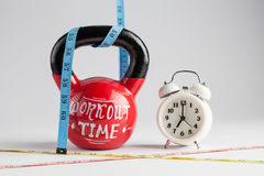 Red kettlebell with Workout Time lettering, traditional alarm cl Stock Photography