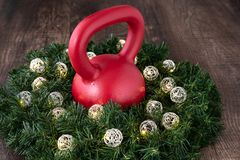 Red kettlebell in a wreath with LED Christmas lights on a wood background royalty free stock image