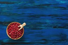 Red kidney beans in wooden dish on dark blue wooden background t royalty free stock photo