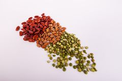 Red kidney pinto lentil beans piled up in white background. Assorted beans kidney pinto lentil raw dry beans piled up in a solid white background stock photos