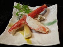 Red king crab seafood. Cooked steam Red king crab seafood with Japanese lemon decorated with green maple leafs on beautiful dish background in restaurant in Stock Image