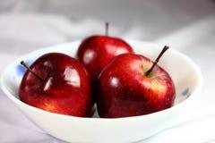 Red kinnaur apples in bowl. Closeup of three ripe red kinnaur apples in white bowl Stock Photos