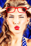Red kiss. Charming pin-up woman with retro hairstyle and make-up sending a kiss Stock Photo